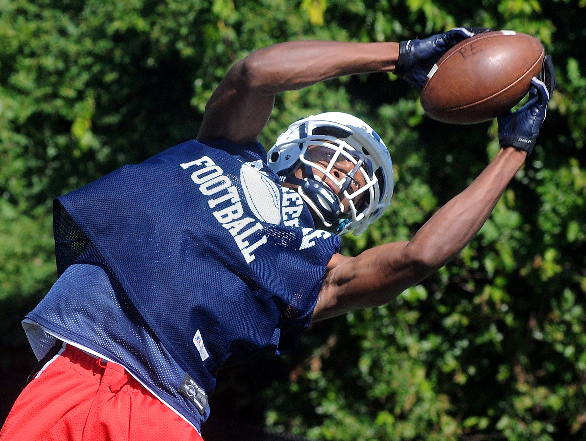 Poughkeepsie High School junior wide receiver Jovan Atkinson goes high in the air to make a catch during his team's second day of football practice on Tuesday. The Pioneers will be playing in Section 9 this season but say they will still play their game.