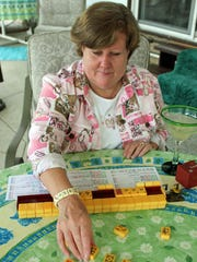 This May 31, 2013 photo shows Judy Palladino handling mahjong pieces during a game night gathering in Mayfield Village, Ohio. For the baby boomer generation, getting together to play games is a way to stay active and social. It also can help people stay mentally sharp.