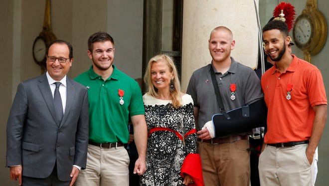 French President Francois Hollande, left, poses with U.S. serviceman Alek Skarlatos, U.S. Ambassador to France Jane Hartley, U.S. serviceman Spencer Stone and U.S. student Anthony Sadler after an honorary ceremony at the Elysee Palace in Paris Aug. 24, 2015.