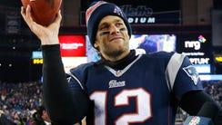 New England Patriots quarterback Tom Brady holds up