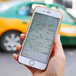 A commuter shows the Didi Chuxing app on her iPhone in Beijing, China, 13 May 2016.
