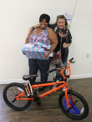 Case manager Yolanda Owens excitedly presents an enrolled client with presents for her son. The gifts included a new bike, fishing rod and other accessories.