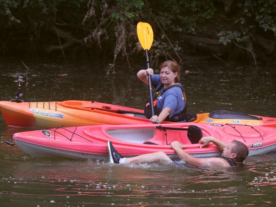 Instructor Andrea White helps David Criswell get back into his kayak as they practice an assisted water rescue June 15, 2017, in Murfreesboro.