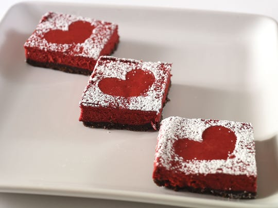 Red Velvet Cheesecake Bars dusted with confectioners' sugar are shown.