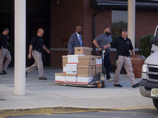 Andrew Ford/staff photo  Investigators used a pallet jack to remove dozens of boxes from the School for Children with Hidden Intelligence in Lakewood. One box was labeled SCHI Invoices 11-12 E-M,? one was labeled SCHI Deposits 08-13.
