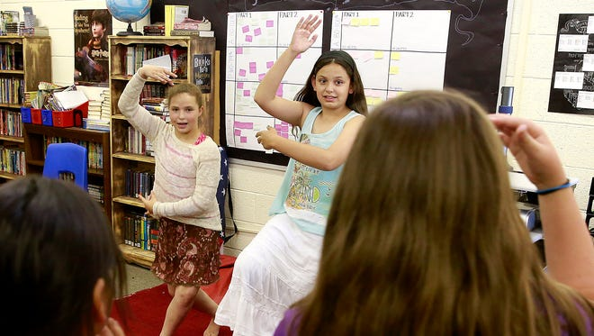 Fifth-graders Kaitlyn Hazell, left, and Samantha Quackenbush perform a traditional Thai dance during Multicultural Day on Thursday at Apache Elementary School.