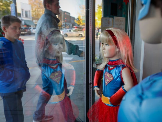 Mannequin in a super girl costume stands in a display window as