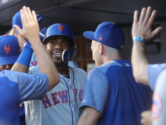Yoenis Cespedes, facing, enters the Mets dugout and returns the high-fives from teammates, including Todd Frazier, after Cespedes hit a solo home run in the third inning against the Yankees on Friday night at Yankee Stadium, July 20, 2018.