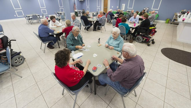 Members of Fraser's community center get in a last game of Euchre Thursday before the center shut amid cuts due to the city's deficit.