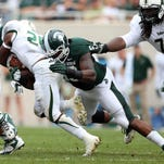 Sep 7, 2013; East Lansing, MI, USA; South Florida Bulls running back Marcus Shaw (20) is tackled by Michigan State Spartans defensive lineman Damon Knox (93) during the first half at Spartan Stadium. Mandatory Credit: Mike Carter-USA TODAY Sports