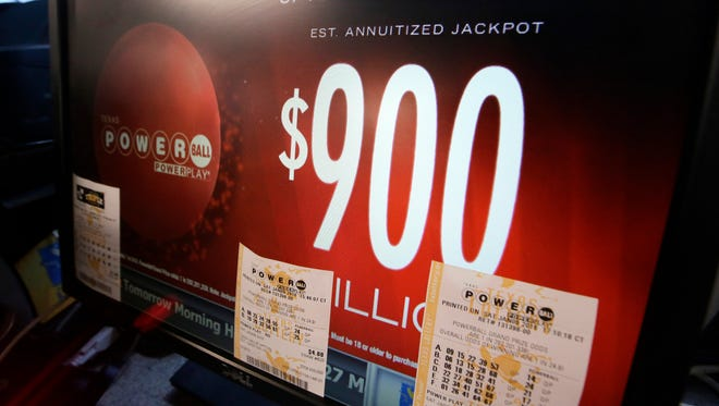 A sign displays the estimated Powerball lottery jackpot amount at a gas station in Dallas, Saturday, Jan. 9, 2016. Ticket sales for the multi-state Powerball lottery soared Saturday in the largest jackpot in U.S. history which grew to $900 million just hours before Saturday night's drawing. (AP Photo/LM Otero)