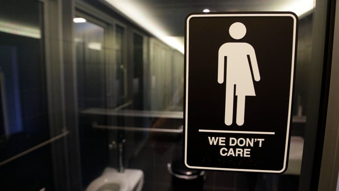 In this photo taken Thursday, May 12, 2016, signage is seen outside a restroom at 21c Museum Hotel in Durham, N.C. North Carolina is in a legal battle over a state law that requires transgender people to use the public restroom matching the sex on their birth certificate. The ADA-compliant bathroom signs were designed by artist Peregrine Honig.