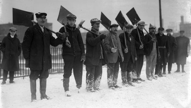 This circa 1915 photo shows a work crew posing in a line with their shovels.