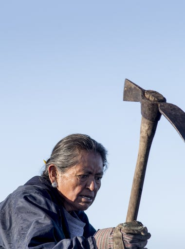 Charlotte Begay, 64, of Shonto, Ariz., breaks up coal with a pickaxe at the public loadout facility at the Kayenta Mine on Feb. 4, 2017. The mine's sole customer is the Navajo Generating Station, a coal-fired power plant near Page, Ariz. If the power plant shuts down it not only would impact plant workers, but coal miners as well.