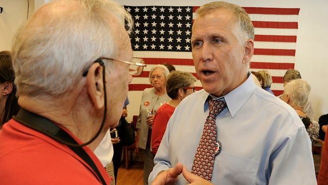Thom Tillis, then speaker of the N.C. House, talks with a supporter at Buncombe County Republican Party headquarters last year during his run for U.S. Senate.