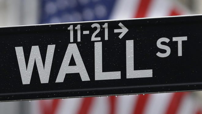 For all the volatility we've experienced this year, stocks are basically flat to modestly up. This July 9, 2015, photo shows a Wall Street sign near the New York Stock Exchange in New York.