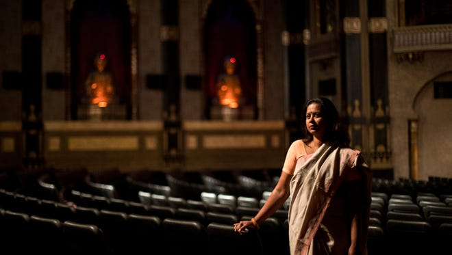 Nirmal Raja poses in Milwaukee's Oriental Theatre as Lois Bielefeld photographs her. They are collaborating in a project that has Bielefeld photographing Raja in her saris at many Milwaukee locations.