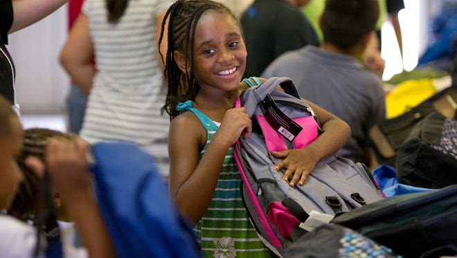 Tanea Wymer picks out a backpack during a previous Operation Hope annual giveaway of school supplies in Fellsmere. The organization is in need of backpacks and school supplies for its Aug. 5 event.