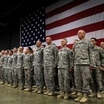 Missouri National Guardsmen line up in formation in front of a flag before they are dismissed during a welcome home ceremony for the Missouri National Guard's 935th Aviation Support Battalion.