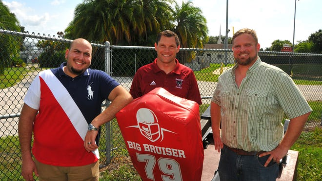 Mechanical engineering students at Florida Tech have built a blocking sled that can record power and the reaction time of players. Mechanical engineer Abdullah Aljanahi, left, and mechanical engineering student Steve Campbell, right, stand with Florida Tech head football coach Steve Englehart with the sled that hooks up to a laptop to record readings.