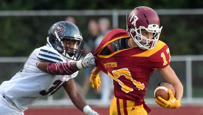 McCutcheon's Colby Phebus is dragged down during Lawrence Central's 40-6 victory at McCutcheon on Friday night.
