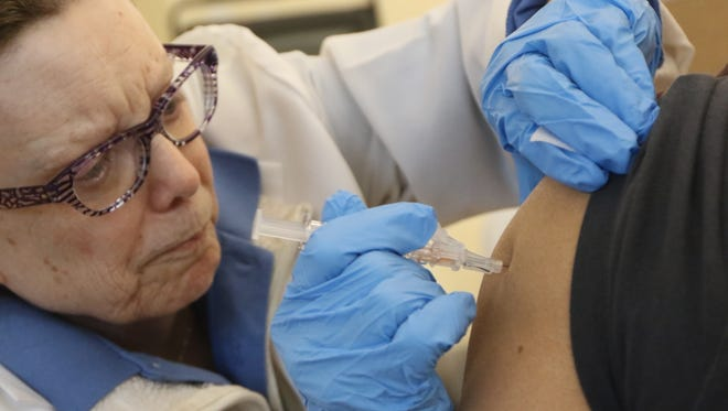 A nurse administers a flu shot. Even though we're already deep in flu season this year and the vaccine is only 36 percent effective, health officials still recommend getting a shot.