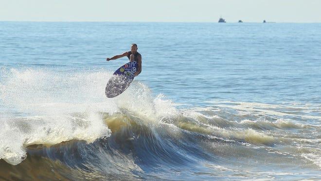 Jason Wilson rides a wave on his skimboard