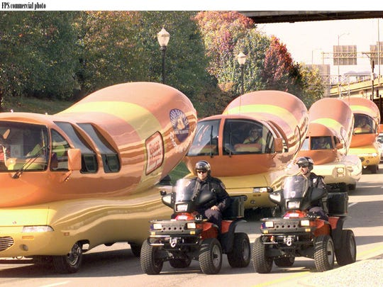 "Six Oscar Mayer Wienermobile vehicles ""linked up"" and the hot dog hot rods paraded through downtown Louisville, KY in 1999 to celebrate the 18 million meals contributed to America's Second Harvest food bank network hrough the ""Share the Smiles"" national grassroots tour."