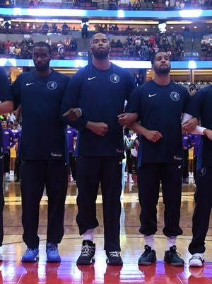 Minnesota Timberwolves players lock arms during the playing of the national anthem before a preseason NBA basketball game against the Los Angeles Lakers.
