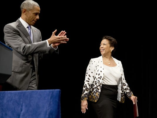 President Barack Obama applauds as Attorney General Loretta Lynch arrives for her investiture ceremony, Wednesday, June 17, 2015, at the Warner Theatre in Washington.