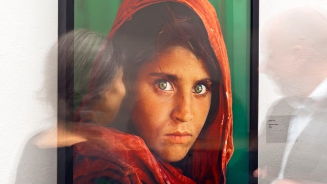 In this picture taken with a long time exposure people walk in front of the photo 'Afghan Girl' (Pakistan, 1984) during the exhibition 'Steve McCurry Retrospective' of US photographer Steve McCurry in the Kunsthalle (Art Hall) in Erfurt, Germany, Wednesday, Feb. 26, 2014.