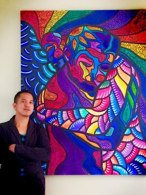 """Artist Marconi Calindas poses with """"You Are Loved,"""" acylic and ink on canvas, 5 feet by 6 feet."""