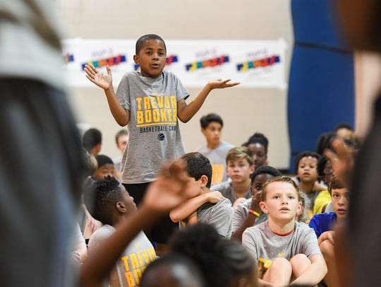 Nine-year-old Omari Dennis asks a question during a