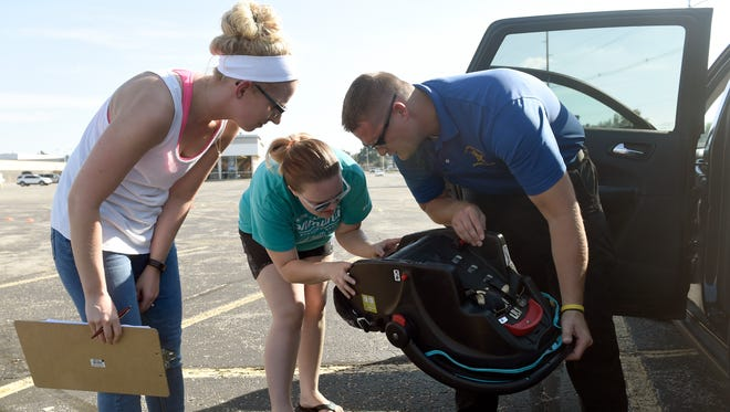 Danielle Dawes, left, and Marissa Wiseman help Vanderburgh County Sheriff's deputy Chris Roe while checking labels on a car seat as the Sheriff's Office hosts a free childhood safety event at Washington Square Mall in Evansville Thursday.  Free child seat inspections were provided as well as a bicycle safety course for kids who received free helmets during the event.