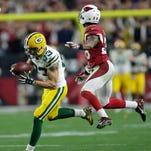Green Bay Packers returner Micah Hyde runs back a punt return against Arizona Cardinals defender Sean Weatherspoon.