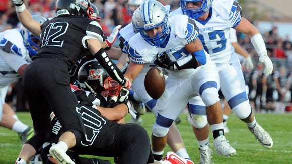 Waukesha West running back Peter MacCudden, second from right is stripped of the ball by Mukego defensive lineman Destin Vitrano near the Muskego goal line during a Classic 8 opener between Muskego and Waukesha West at Muskego Thursday, Sept. 1.