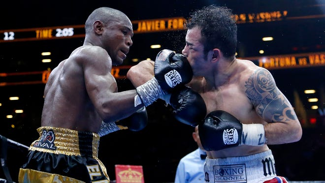 Javier Fortuna, left, lands a right on Bryan Vasquez during the 12th round Friday night. ( Photo: Julio Cortez, AP)