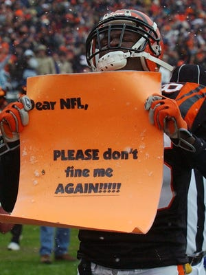 Bengals receiver Chad Johnson holds a sign asking the NFL not to fine him after scoring on a 10-yard reception against the San Francisco 49ers in December of 2003.