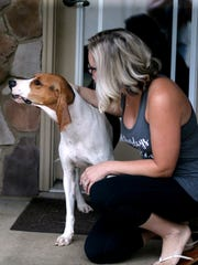 Brittney Babbitt, who rescued a coonhound named Hope, consoles the dog, who is a bit skittish around the clicking sound of a camera.