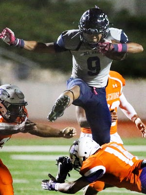 Del Valle running back Adrian Vazquez, 9, leaps over Eastlake defensive back Montrill Williams, 14, on his way to more yardage Friday night at the Socorro Activities Complex.