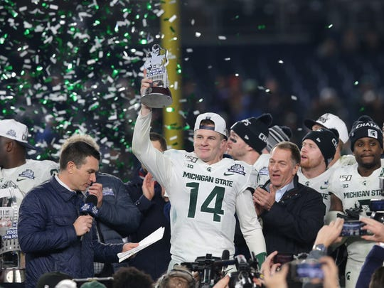 Michigan State quarterback Brian Lewerke holds the MVP trophy after defeating Wake Forest in the Pinstripe Bowl at Yankee Stadium in New York, Dec. 27, 2019.