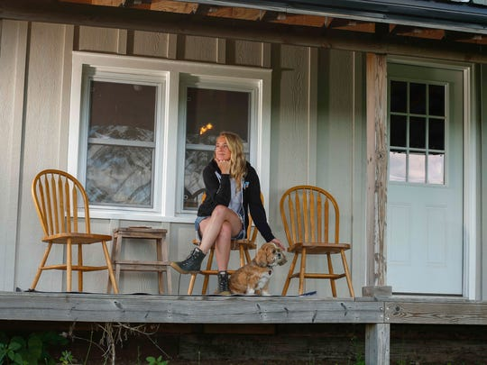 Lissie Maurus, a folk musician originally from the Quad Cities, poses for a portrait on one of the porches of her northeast Iowa farmhouse alongside her dog, Byron. Lissie recently returned to the Midwest after spending a decade in Colorado and California working on her music career.