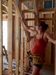 """New homeowner Kelda Harrison shows off the stairs she helped build for her future home in Swannanoa. Harrison is part of Mountain Housing Opportunities' Self-Help Homeownership Program, which allows low-income families to build their own neighborhoods. The """"sweat-equity"""" is then exchanged for competitive mortgages and low-interest rates."""