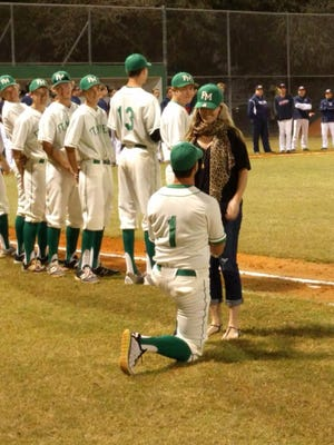 Fort Myers assistant baseball coach Steve Cato proposes to his girlfriend, Kiersten Koza, at a home baseball game on Feb. 12.
