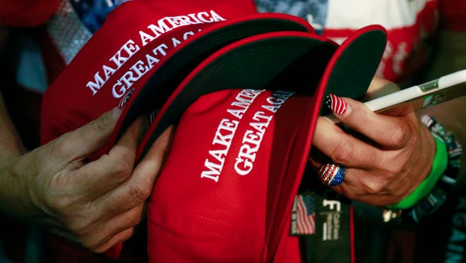 FILE - In this June 2, 2016, file photo, a woman holds hats to get them autographed by Republican presidential candidate Donald Trump during a rally in San Jose, Calif. The New York Post reported on March 19, 2017, that a Philadelphia man sued a New York City bar, claiming he was denied service for wearing such a hat.  (AP Photo/Jae C. Hong, File)
