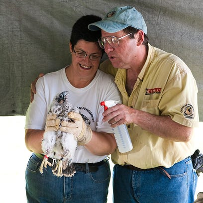 Gwen and Dennis Patrick hold Gwenis, a peregrine falcon