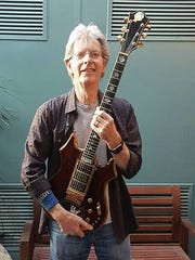 "Phil Lesh holds Jerry Garcia's ""Tiger"" guitar, now owned by Jim Irsay."