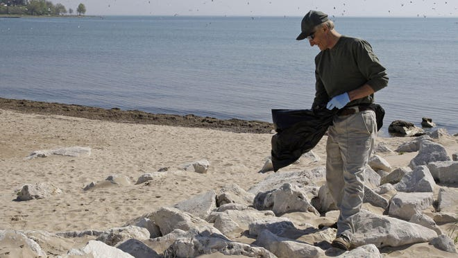 Bill Steffen of Sheboygan picks up trash on the Deland Park beach in 2014. The annual September adopt-a-beach cleanup will be from 9 a.m. until noon on Saturday, Sept. 19, at Deland Park Beach near Broughton Drive, Sheboygan.