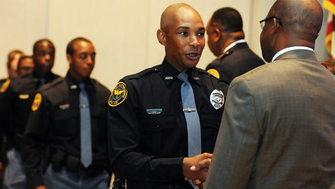 Graduating recruit Harry Crockett, left, shakes hands with Hattiesburg Mayor Johnny DuPree as members of recruit class 31 receive their badges during the Hattiesburg Police Department's graduation ceremony at the Lake Terrace Convention Center.