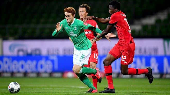 Joshua Sargent, left, of Bremen challenges Edmond Tapsoba of Leverkusen during the German Bundesliga soccer match between Werder Bremen and Bayer Leverkusen 04 in Bremen, Germany, Monday, May 18, 2020. The German Bundesliga becomes the world's first major soccer league to resume after a two-month suspension because of the coronavirus pandemic.